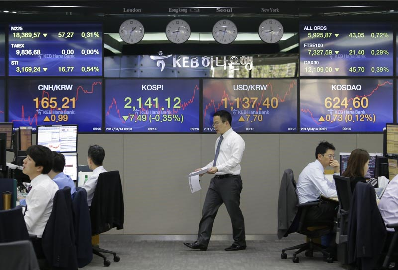 A currency trader passes by screens showing the Korea Composite Stock Price Index (KOSPI), center left, and foreign exchange rate, center right, at the foreign exchange dealing room of the KEB Hana Bank headquarters in Seoul, South Korea, Friday, April 14, 2017. Photo: AP