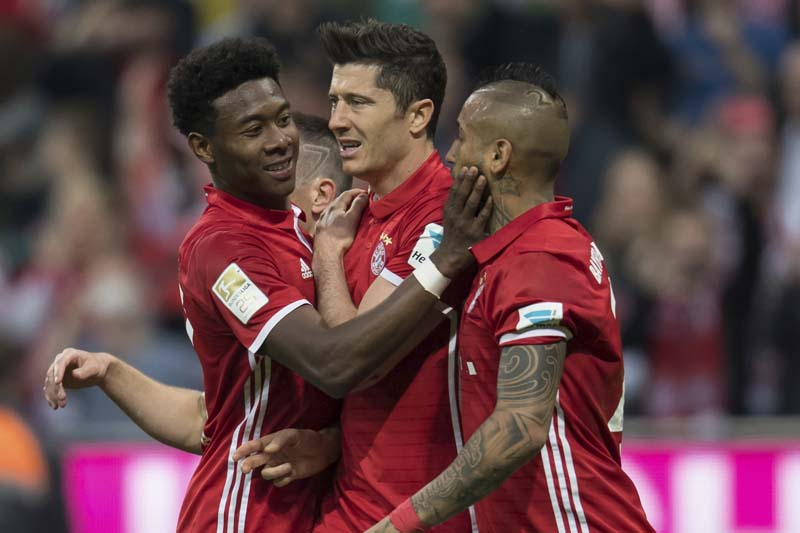 Bayern's Robert Lewandowski (centre), holds his shoulder as he celebrates after scoring his side's fourth goal during the German Bundesliga soccer match between FC Bayern Munich and Borussia Dortmund in Munich, Germany, on Saturday, April 8, 2017. Photo: AP