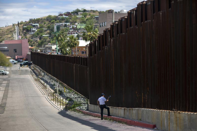 In this April 1, 2017, photo, a man in Nogales, Ariz., talks to his daughter and her mother who are standing on the other side of the border fence in Nogales, Mexico. Homeland Security Secretary John Kelly says arrests of people entering the United States illegally across the Mexican border plummeted in March 2017. That's a signal that fewer people are trying to sneak into the US. Photo: AP