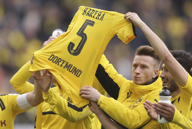 Borussia Dortmund's Marco Reus, Nuri Sahin (right) and other players hold up the jersey of teammate Marc Bartra after the German Bundesliga soccer match between Borussia Dortmund and Eintracht Frankfurt in Dortmund, Germany, on Saturday, April 15, 2017. Photo: Ina Fassbender/dpa via AP