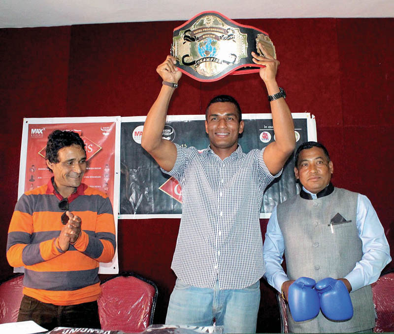 Manohar Basnet holds aloft the belt of Champion of Champions during a press meet in Kathmandu on Tuesday. Photo: THT