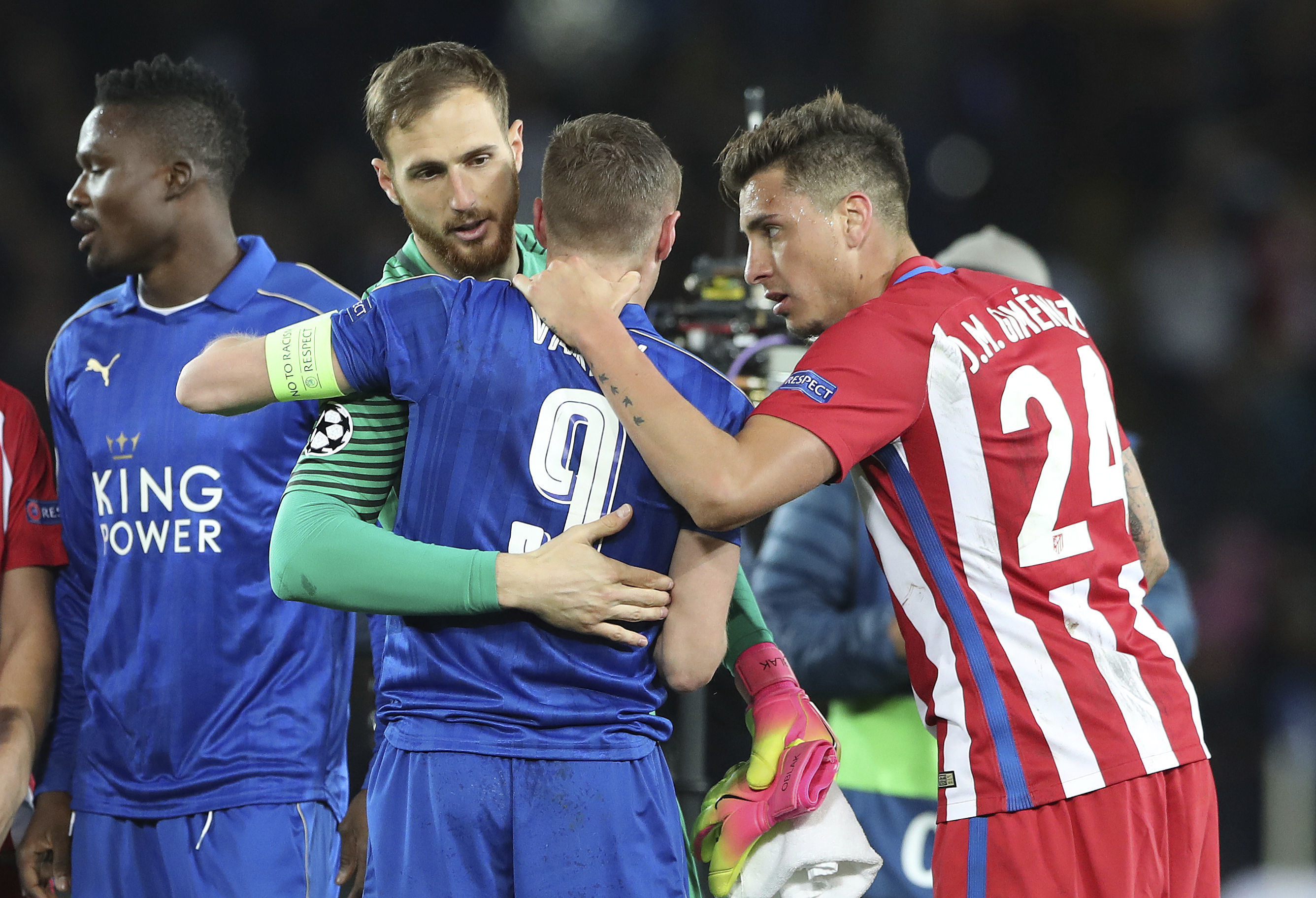 Leicester City's Jamie Vardy, centre, is consoled by Atletico Madrid's Jan Oblak and Jose Maria Gimenez, right, after the the second leg of the UEFA Champions League quarter final soccer match between Leicester City and Atletico Madrid at the King Power Stadium in Leicester, Tuesday April 18, 2017. The match ended a 1-1 draw with Atletico advancing to the semifinals 2-1 on aggregate. (Nick Potts/PA via AP)
