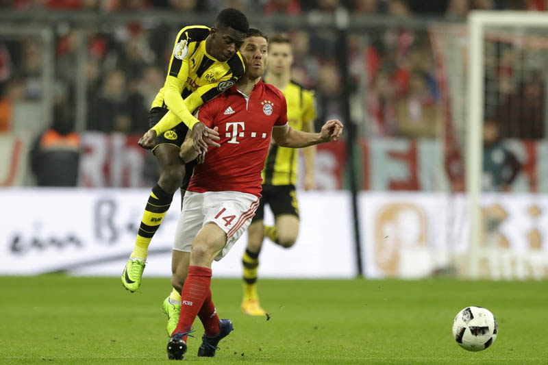 Dortmund's Ousmane Dembele (left), and Bayern's Xabi Alonso challenge for the ball during the German Soccer Cup semifinal match between FC Bayern Munich and Borussia Dortmund at the Allianz Arena stadium in Munich, Germany, on Wednesday, April 26, 2017. Photo: AP
