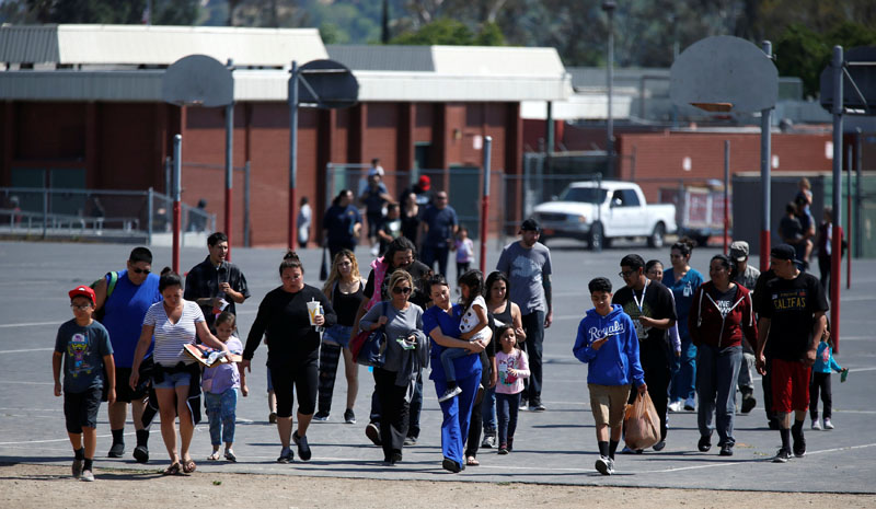 Students who were evacuated after a shooting at North Park Elementary School walk with their waiting parents at a high school in San Bernardino, California, US, on April 10, 2017. Photo: Reuters