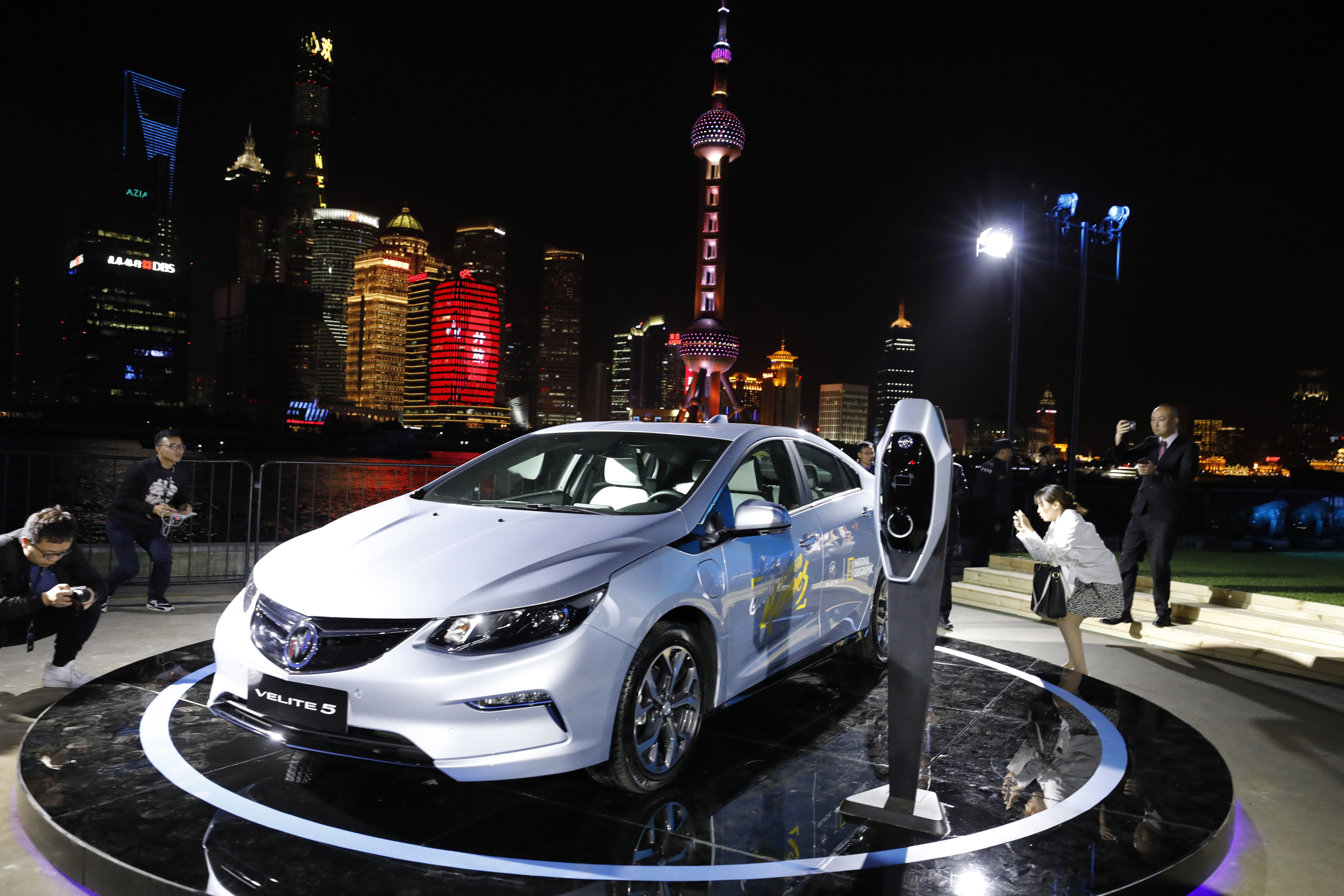 Visitors take photos of the Buick Velite 5, an extended range electric hybrid, during a global launch event ahead of the Shanghai Auto 2017 show in Shanghai, China, Tuesday, April 18, 2017. At the auto show, the global industry's biggest marketing event of the year, almost every global and Chinese auto brand is showing at least one electric concept vehicle, if not a market-ready model. (AP Photo/Ng Han Guan)