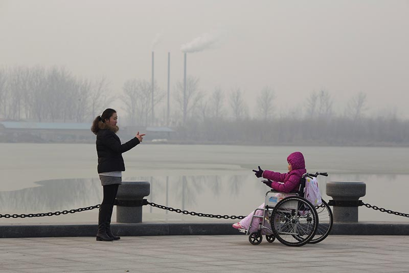 FILE - Visitors to a park gestures at each other near chimneys spewing smoke in Beijing, China, on Saturday, December 12, 2015. Photo: AP