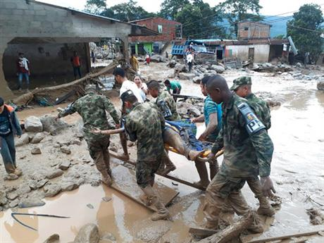 In this handout photo released by the Colombian National Army, soldiers carry a victim on a stretcher, in Mocoa, Colombia, Saturday, April 1, 2017, after an avalanche of water from an overflowing river swept through the city as people slept. The incident triggered by intense rains left at least 100 people dead in Mocoa, located near Colombia's border with Ecuador. (Colombian Army Photo via AP)n