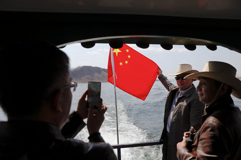 Tourists pose with Chinese flag on a boat taking them from the Chinese side of the Yalu River for sightseeing close to the the shores of North Korea, near Dandong, China's Liaoning province, April 1, 2017. Photo: Reuters