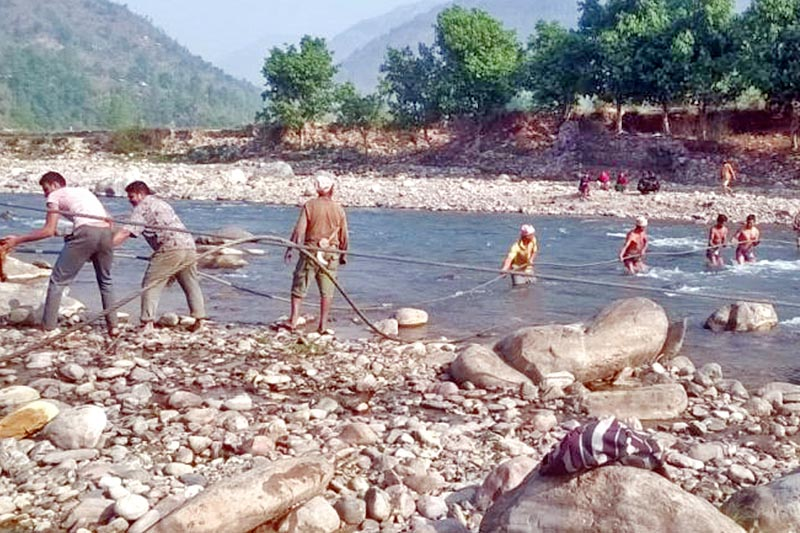 Locals pull ropes for the construction of a suspension bridge over a river at Sudighat in Gulmi district, on Thursday, April 13, 2017. Photo: RSS