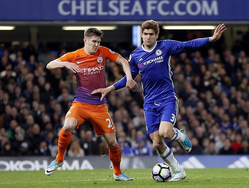 Manchester City's John Stones (left) and Chelsea's Marcos Alonso (right) challenge for the ball during the English Premier League soccer match between Chelsea and Manchester City at the Stamford Bridge stadium in London, Great Britain, on Wednesday, April 5, 2017. Photo: AP