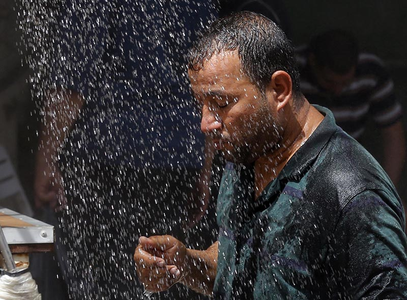 FILE - An Iraqi man cools off the summer heat by using an open air shower in Baghdad, Iraq, on July 20, 2016. Photo: AP
