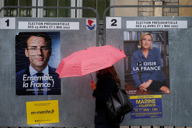 A woman walks past the new official posters for the candidates for the 2017 French presidential election, Emmanuel Macron, head of the political movement En Marche !, or Onwards !, (left) and Marine Le Pen, French National Front (FN) political party leader (right), in Paris, France, on April 28, 2017. Photo: Reuters