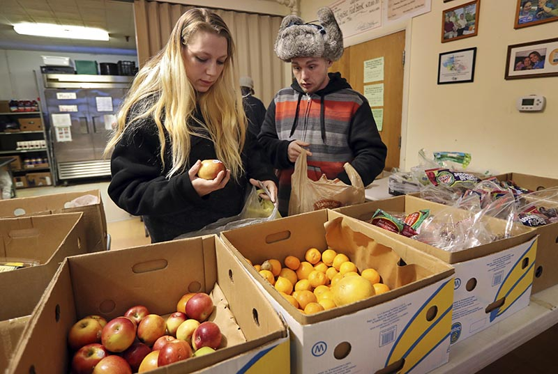 Sunny Larson (left) and Zak McCutcheon pick produce while gathering provisions to take home at the Augusta Food Bank in Augusta, Maine. Republican Governor, on Monday, March 27, 2017. Photo: AP