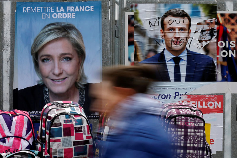 A woman walks past official posters of candidates for the 2017 French presidential election Marine Le Pen, French National Front (FN) political party leader (L) and Emmanuel Macron, head of the political movement En Marche !, or Onwards !, (R) on a local market in Bethune, France on April 24, 2017. Photo: Reuters