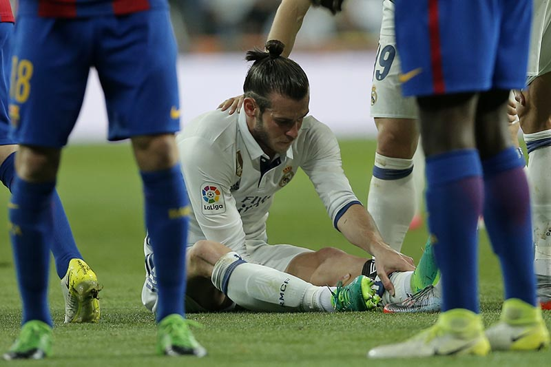 Real Madrid's Gareth Bale holds his leg after getting injured during a Spanish La Liga soccer match between Real Madrid and Barcelona, dubbed 'el clasico', at the Santiago Bernabeu stadium in Madrid, Spain, on Sunday, April 23, 2017. Photo: AP