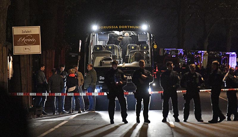 FILE -  Police officers stand in front of Dortmund's damaged team bus after explosions which injured two people before the Champions League quarterfinal soccer match between Borussia Dortmund and AS Monaco in Dortmund, western Germany, on April 11, 2017. Photo: AP