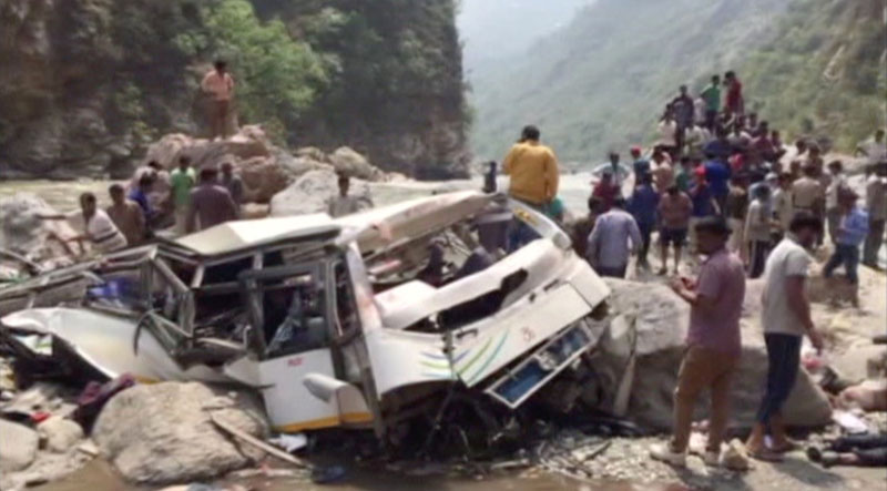 People and police gather at the site where a bus fell off a mountain road in Shimla, Himachal Pradesh, India on April 19, 2017 in this still image taken from video. Photo: ANI via Reuters TV