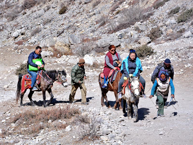 Tourists are seen riding on horses on their way to Muktinath in Mustang district, on Sunday, April 9, 2017. Photo: RSS