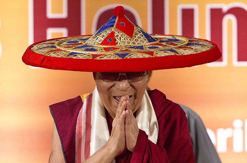 Tibetan spiritual leader Dalai Lama wears a Japi, a traditional Assamese head gear, and greets the audience during the platinum jubilee celebrations of Assam Tribune newspaper in Gauhati, India, on Saturday, April 1, 2017. Photo: AP