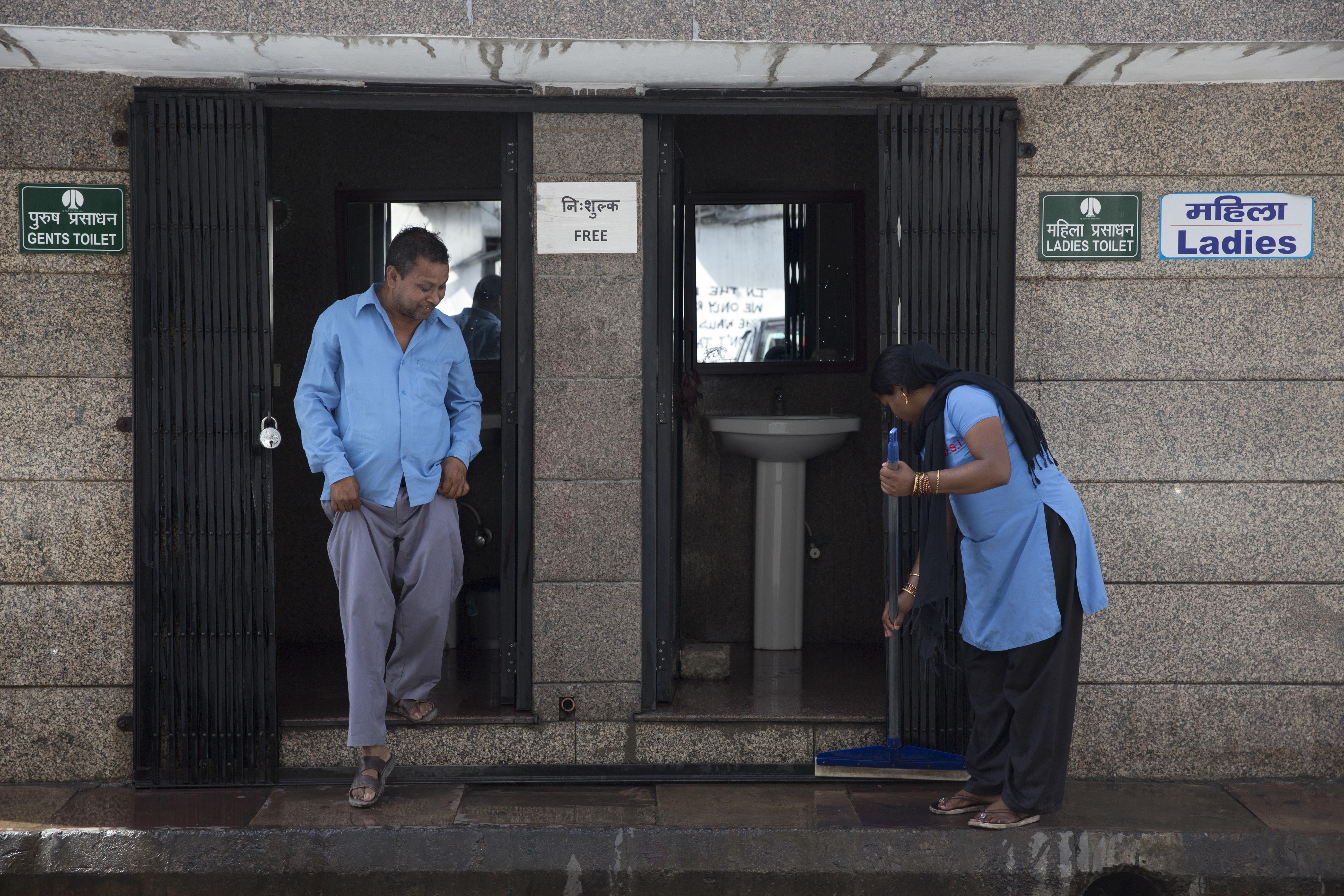 An Indian municipal worker cleans a public toilet as a man walks out in New Delhi, India, on Thursday, April 6, 2017. Photo: AP