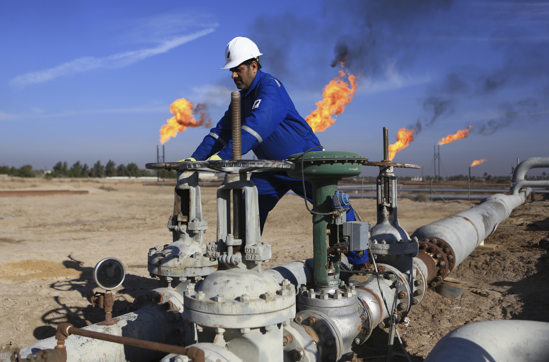 An Iraqi worker operates valves in Nihran Bin Omar field north of Basra, 340 miles (550 kilometers) southeast of Baghdad, Iraq, on January 12, 2017. Photo: AP/File