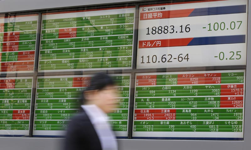 A woman walks past an electronic stock board showing Japan's Nikkei 225 index at a securities firm in Tokyo, Tuesday, April 4, 2017.  Asian stock markets were mostly lower on Tuesday after disappointing US car sales data contributed to a bleak day on Wall Street. Investors are cautiously awaiting President Donald Trump's meeting with the Chinese president later this week. Photo: AP