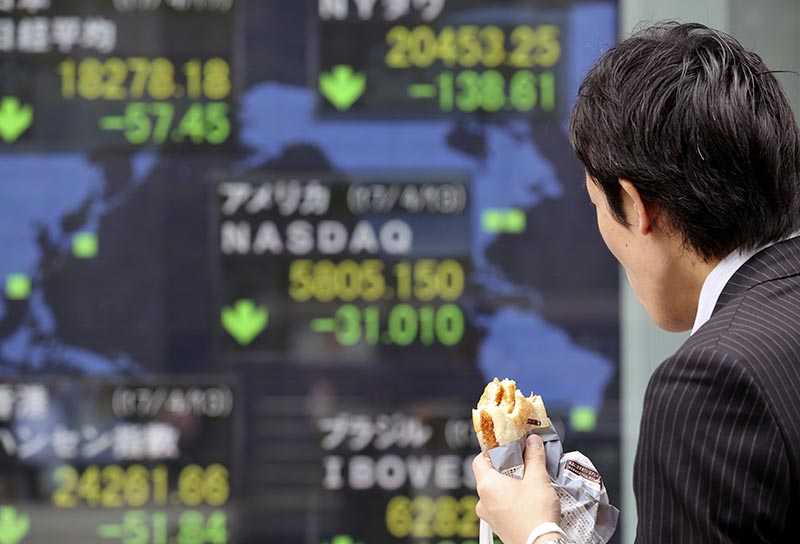 A man looks at an electronic stock board of a securities firm in Tokyo, on Monday, April 17, 2017. Photo: AP