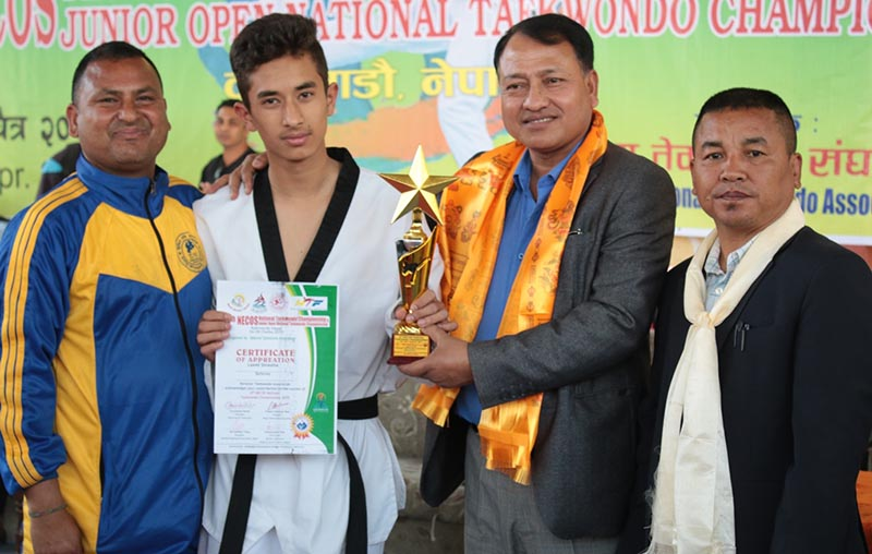 NSC Member Secretary Keshab Kumar Bista handing over the best playeru2019s trophy to Kapil Sharma after the fourth NECOS National Taekwondo Championship in Kathmandu on Monday, April 10, 2017. Photo: THT