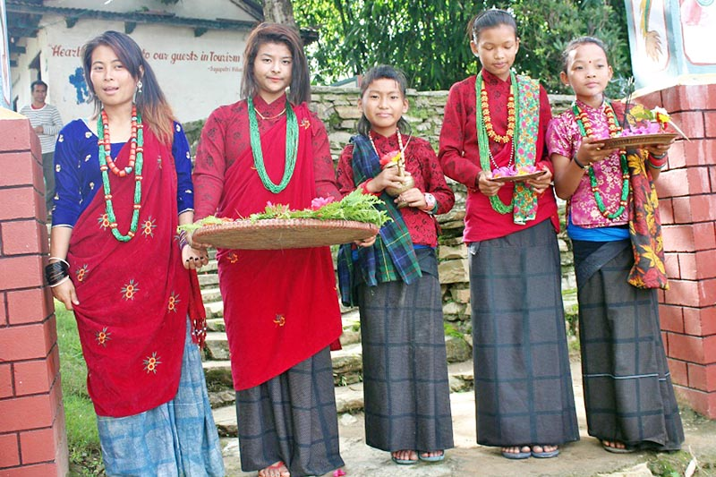 Locals clad in traditional attires await to welcome tourists visiting Lamjung district to their homes at Kaulepani in the district, on Sunday, April 2, 2017. Photo: RSS