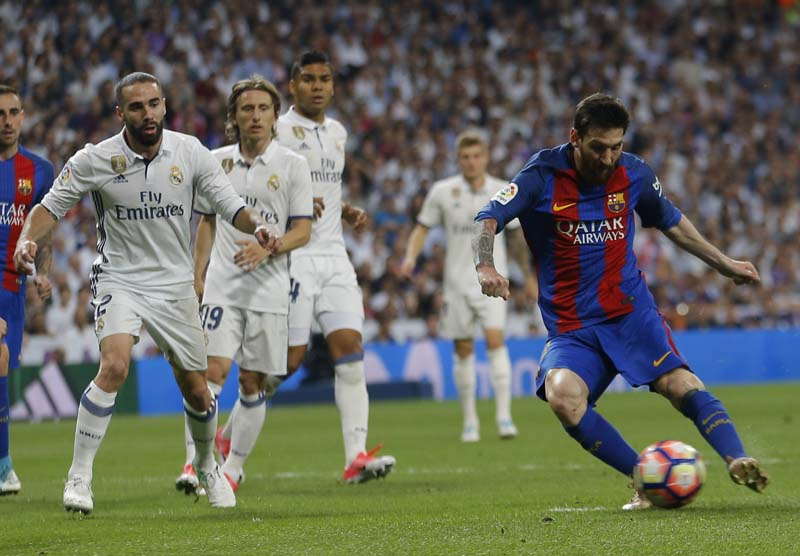 Barcelona's Lionel Messi (right), scores during a Spanish La Liga soccer match between Real Madrid and Barcelona, dubbed 'el clasico', at the Santiago Bernabeu stadium in Madrid, Spain, on Sunday, April 23, 2017. Photo: AP