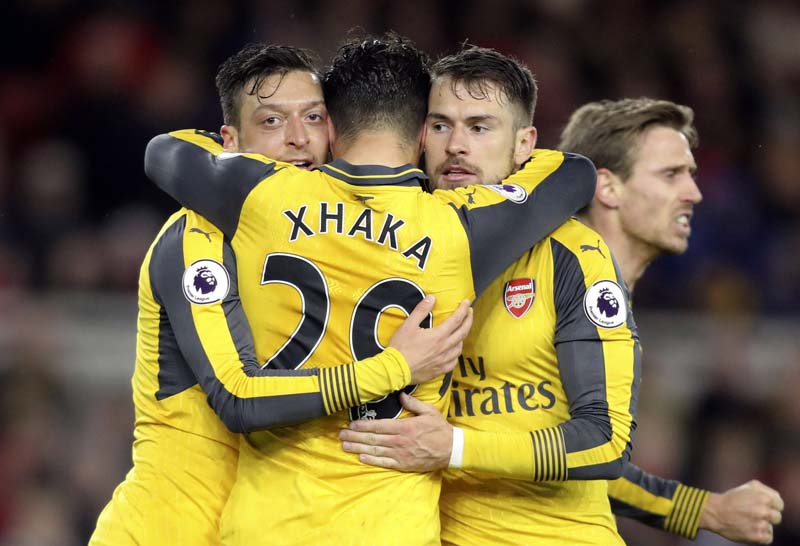Arsenal's Mesut Ozil (left), celebrates with teammates after scoring against Middlesbrough during the English Premier League soccer match at the Riverside Stadium, Middlesbrough, England, on Monday April 17, 2017. Photo: Owen Humphreys/PA via AP