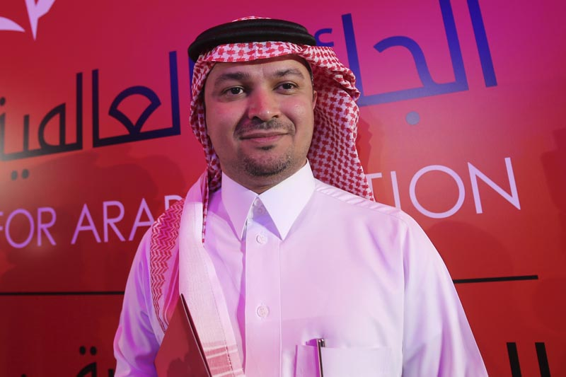Mohammed Hasan Alwan, Saudi Arabia's novelist poses in front of cameras after he won the International Prize for Arabic Fiction (IPAF) in Abu Dhabi, United Arab Emirates, Tuesday, April 25, 2017. Photo: AP