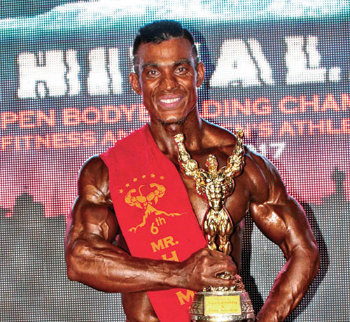 Ashok Maharjan holds the trophy after winning the sixth Mr Himalaya National Open nBodybuilding Tournament in Kathmandu, on April 08, 2017.