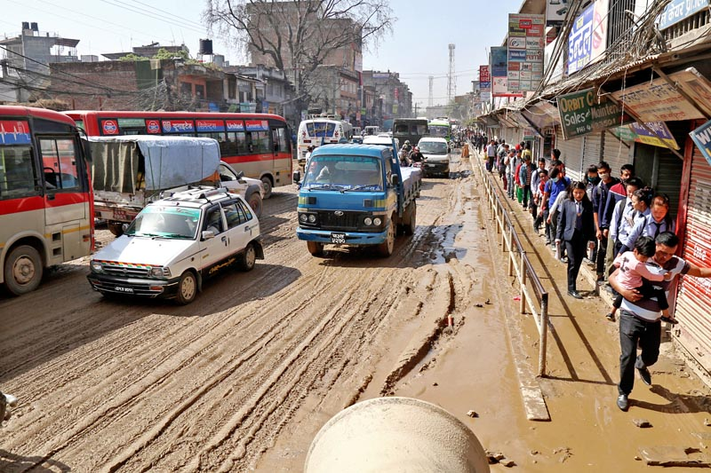 Vehicles ply a muddy road in Chabahill of Kathmandu after water was poured to control the dust casued by the construction works for the Melamchi Water Supply Project on Sunday, April 9, 2017. Photo: RSS