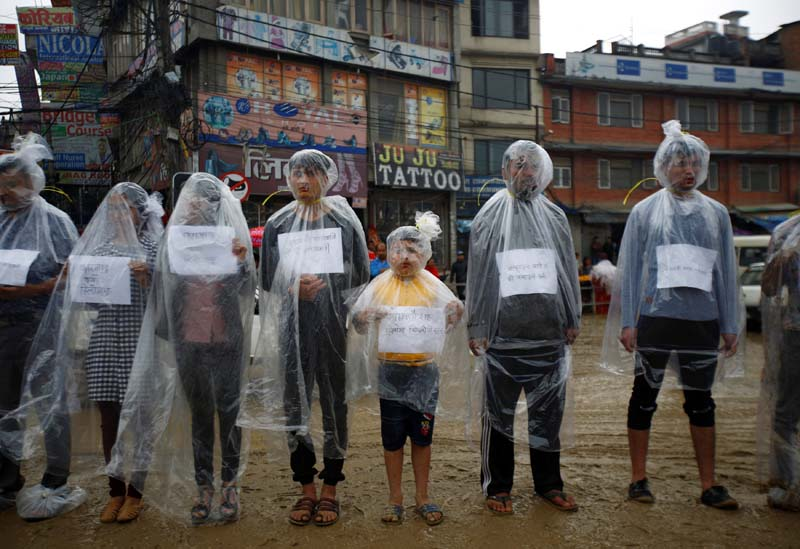 Activists take part in a demonstration to mark Earth Day by covering themselves in plastic sheets to protest against air pollution and muddy roads caused by what they say is a road expansion project in Kathmandu, Nepal, on April 22, 2017. Photo: Navesh Chitrakar via Reuters