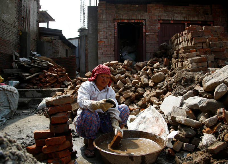 A woman cleans bricks collected from her house that collapsed during the 2015 earthquake, to rebuild her house in Bhaktapur, Nepal, on April 21, 2017. Photo: Reuters