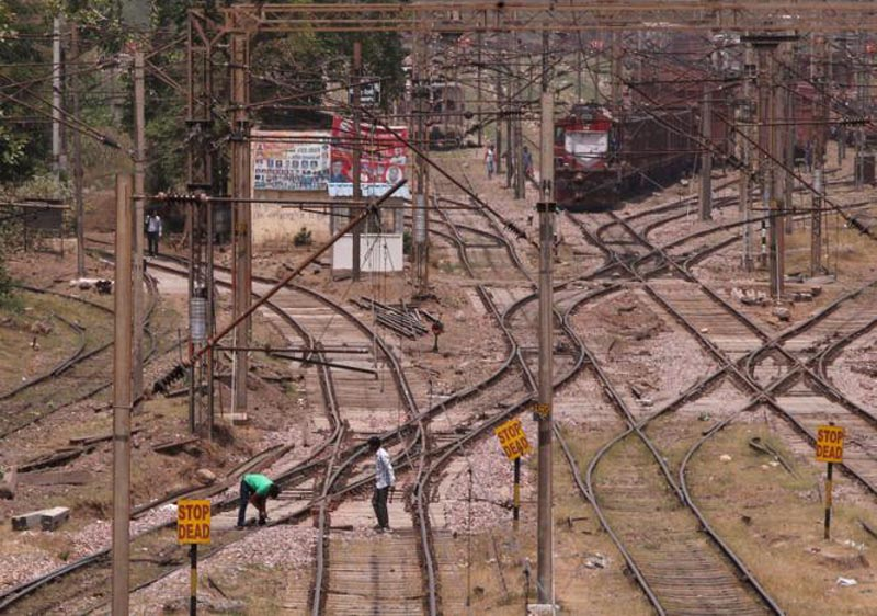Railway employees work on tracks as a freight train approaches at Tughlakabad railway station in New Delhi, India, April 20, 2017. Photo: Reuters