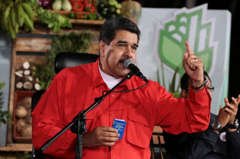 Venezuela's President Nicolas Maduro holds a copy of the Venezuelan constitution as he speaks during a meeting in Caracas, Venezuela April 7, 2017. Photo: Miraflores Palace via Reuters