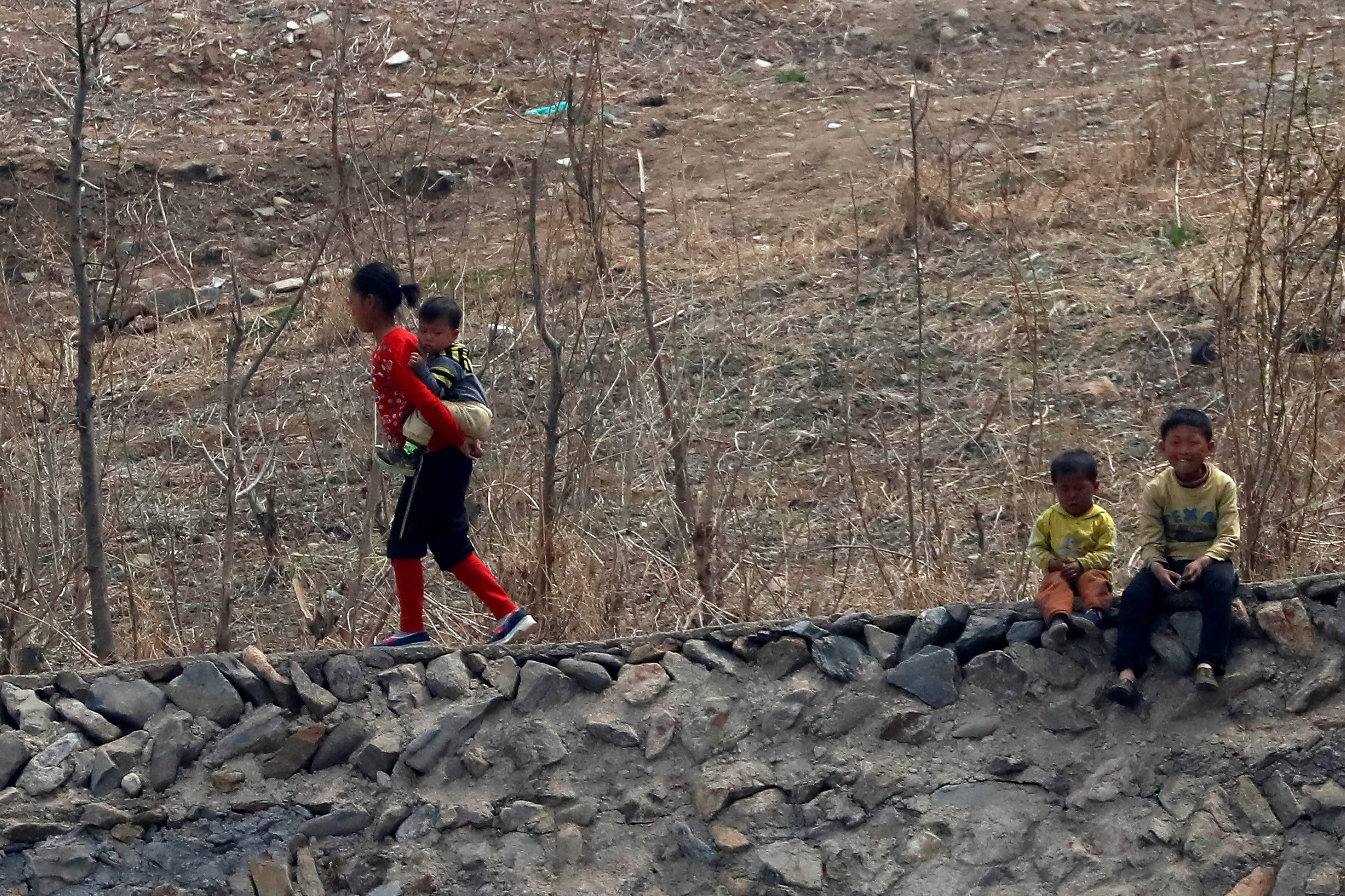 A North Korean girl carries an infant on her back while two children sit on a ledge on the banks of the Yalu River in Sinuiju, North Korea, on April 16, 2017. Photo: Reuters