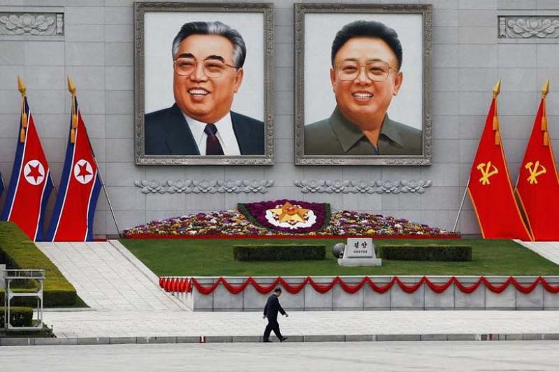 A man walks in front of portraits of North Korea founder Kim Il Sung and late leader Kim Jong Il in central Pyongyang, North Korea, on April 16, 2017. Photo: Reuters