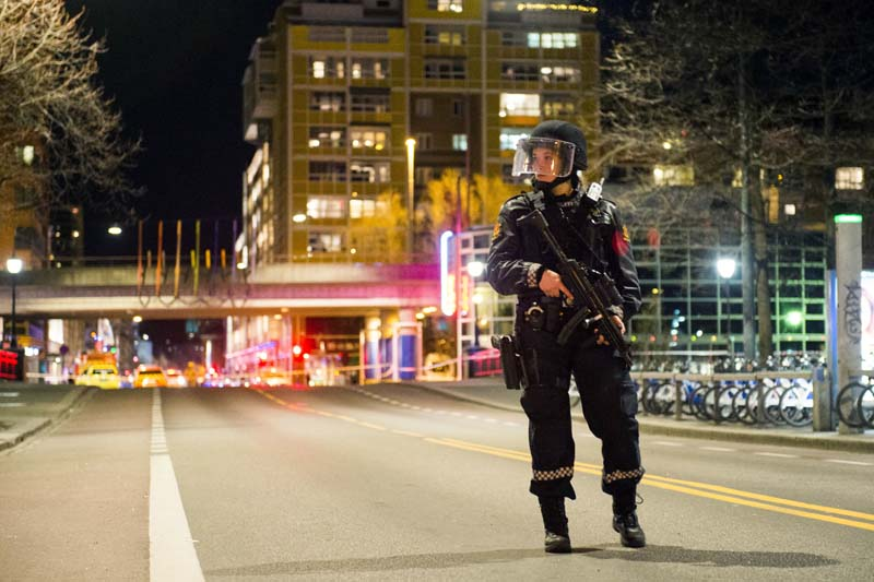 An officer stands guard as police cordon off a large area around a subway station on a busy commercial street, in Oslo, Norway, on Saturday night, April 8, 2017. Photo: AP
