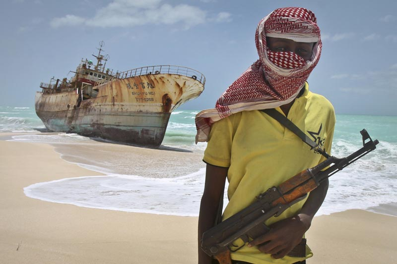 FILE - In this Sunday, Sept. 23, 2012 file photo, masked and armed Somali pirate Hassan stands near a Taiwanese fishing vessel washed ashore after the pirates were paid a ransom and the crew were released in the once-bustling pirate den of Hobyo, Somalia. Photo: AP