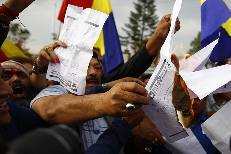 Rastriya Prajatantra Party cadres burn a copy of Election Commission's decision on the party's statute during a protest in Kathmandu on Tuesday, April 18, 2017.