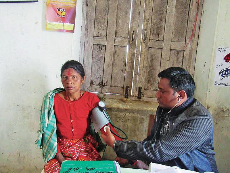Dr Rup Chandra BK examining a patient at a health post in Barhabisha, Bajura, on Friday, April 14, 2017. Photo: THT