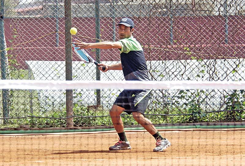 Anil Shahi returns to Subrat Basnet during their fifth Citizensu0092 Bank Open Tennis Tournament match in Lalitpur on Monday. Photo: Naresh Shrestha/THT