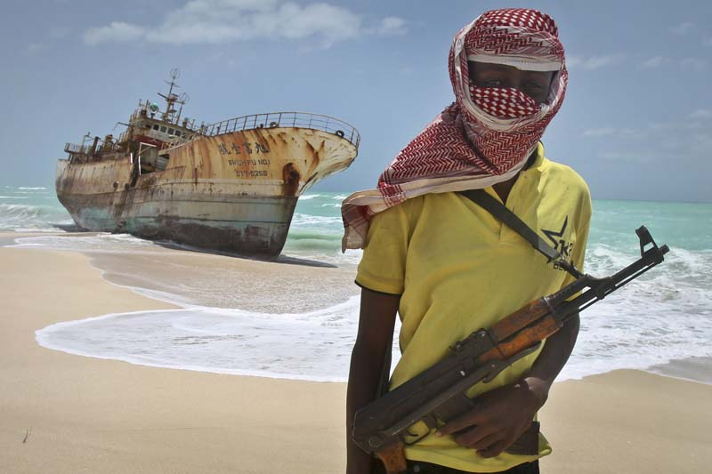 Masked Somali pirate Hassan stands near a Taiwanese fishing vessel that washed up on shore after the pirates were paid a ransom and released the crew, in the once-bustling pirate den of Hobyo, Somalia, Sunday, September 23, 2012. Photo: AP