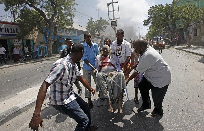 FILE - Rescuers carry away a man who was wounded in a suicide car bomb attack in Mogadishu, Somalia, on Monday, March 13, 2017. Photo: AP