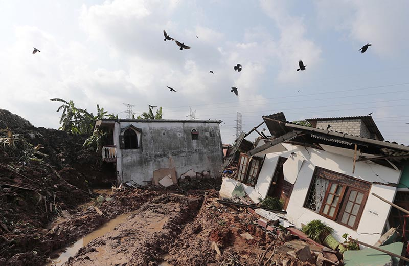 Crows fly over a row of houses buried by a collapse of a garbage dump in Meetotamulla, on the outskirts of Colombo, Sri Lanka, on Saturday, April 15, 2017. Photo: AP