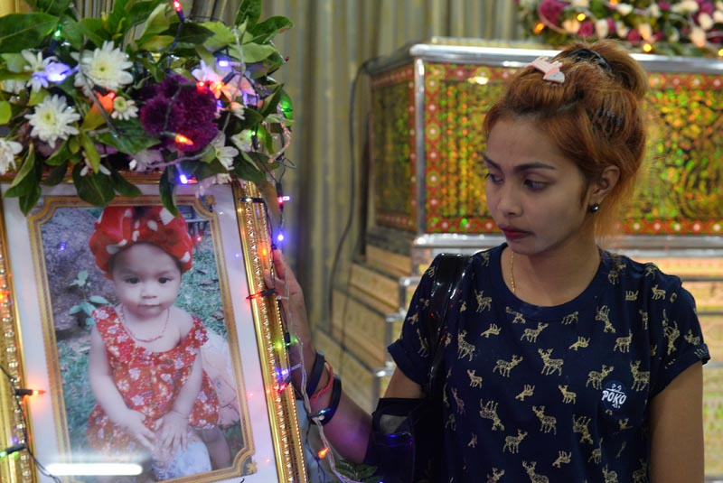 Jiranuch Trirat, mother of 11-month-old daughter who was killed by her father who broadcast the murder on Facebook, stands next to a picture of her daughter at a temple in Phuket, Thailand, on April 25, 2017. REUTERS/Sooppharoek Teepapan  FOR EDITORIAL USE ONLY. NO RESALES. NO ARCHIVES