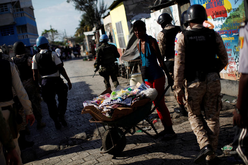 A woman pushing a wheelbarrow carries her goods as she passes between UN peacekeepers and Haitian national police officers and members of UNPOL (United Nations Police) during a patrol in Cite Soleil in Port-au-Prince, Haiti, on March 3, 2017. Photo: Reuters